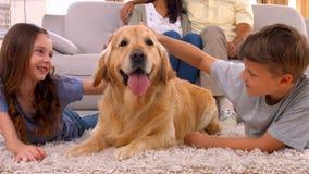 Szczęśliwy rodzinny ono uśmiecha się z ich psem zbiory