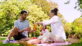 Szczęśliwy rodzinny pije sok na pinkinie przy parkiem zbiory