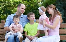 Szczęśliwy rodzinny portret na plenerowym, grupa pięć ludzi siedzi na drewnianej ławce w miasto parku, lato sezonie, dziecku i ro Fotografia Stock