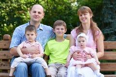 Szczęśliwy rodzinny portret na plenerowym, grupa pięć ludzi siedzi na drewnianej ławce w miasto parku, lato sezonie, dziecku i ro Obrazy Royalty Free