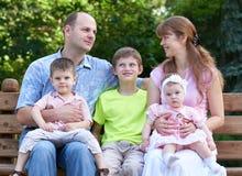 Szczęśliwy rodzinny portret na plenerowym, grupa pięć ludzi siedzi na drewnianej ławce w miasto parku, lato sezonie, dziecku i ro Fotografia Royalty Free