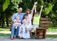 Szczęśliwy rodzinny portret na plenerowym, grupa pięć ludzi siedzi na drewnianej ławce w miasto parku, lato sezonie, dziecku i ro Zdjęcia Stock