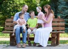 Szczęśliwy rodzinny portret na plenerowym, grupa pięć ludzi siedzi na drewnianej ławce w miasto parku, lato sezonie, dziecku i ro Zdjęcie Stock