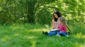 Szczęśliwy Rodzinny portret Outdoors w miasto parku z Białym laptopem Atrakcyjna mała dziewczynka z Kędzierzawym blondynem Uczy s zbiory