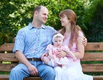 Szczęśliwy rodzinny portret z dziewczynką na plenerowym, siedzi na drewnianej ławce w miasto parku, lato sezonie, dziecku i rodzi Obrazy Royalty Free