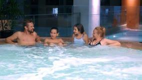 Szczęśliwy rodzinny relaksować w plenerowym jacuzzi dwa dziecko nastolatka, kobieta i mężczyzna relaksuje w gorącej wodzie blisko zbiory wideo