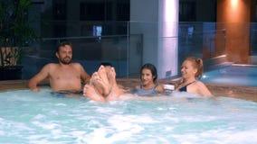 Szczęśliwy rodzinny relaksować w plenerowym jacuzzi dwa dziecko nastolatka, kobieta i mężczyzna relaksuje w gorącej wodzie blisko zdjęcie wideo