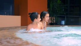 Szczęśliwy rodzinny relaksować w plenerowym jacuzzi dwa dziecko nastolatka relaksuje w gorącej wodzie blisko basenu zbiory wideo