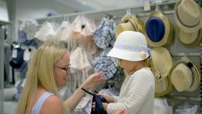 Szczęśliwy rodzinny robi zakupy Rodzina w centrum handlowym Macierzysty pomagać jej córki wybierać odzieżowego w sklepie dzieci o zbiory wideo