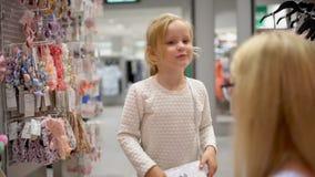 Szczęśliwy rodzinny robi zakupy Rodzina w centrum handlowym Macierzysty pomagać jej córki wybierać odzieżowego w sklepie dzieci o zbiory