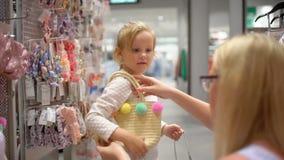 Szczęśliwy rodzinny robi zakupy Rodzina w centrum handlowym Macierzysty pomagać jej córki wybierać odzieżowego w sklepie dzieci o zdjęcie wideo