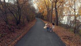 Szczęśliwy rodzinny spacer przy parkiem przy jesienią z małą dziecko anteną zbiory