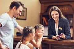 Szczęśliwy rodzinny sprawdzać w hotelu przy recepcyjnym biurkiem zdjęcie royalty free
