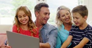 Szczęśliwy rodzinny używa laptop w żywym pokoju zbiory wideo