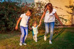Szczęśliwy rodzinny wydaje czas outdoors chodzi w parku Macierzysty i jej synu trzyma małej berbeć dziewczyny dzień macierzysty s zdjęcia royalty free