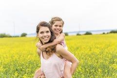 Szczęśliwy rodziny dziecka i matki córki uścisk na kolorów żółtych kwiatach na naturze w lecie Zdjęcie Stock