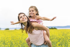 Szczęśliwy rodziny dziecka i matki córki uścisk na kolorów żółtych kwiatach na naturze w lecie Zdjęcia Royalty Free