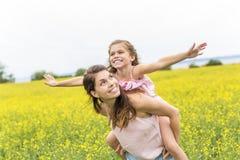 Szczęśliwy rodziny dziecka i matki córki uścisk na kolorów żółtych kwiatach na naturze w lecie Fotografia Royalty Free