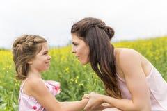 Szczęśliwy rodziny dziecka i matki córki uścisk na kolorów żółtych kwiatach na naturze w lecie Obrazy Royalty Free