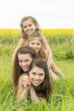 Szczęśliwy rodziny matki i childs córki uścisk na kolorów żółtych kwiatach na naturze w lecie Zdjęcie Royalty Free