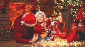 Szczęśliwy rodziny matki ojciec i dziecko przy choinką w domu Fotografia Royalty Free