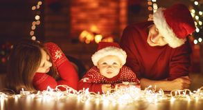 Szczęśliwy rodziny matki ojciec i dziecko przy choinką w domu Zdjęcie Stock