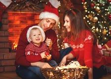 Szczęśliwy rodziny matki ojciec i dziecko przy choinką w domu Zdjęcia Royalty Free