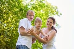 Szczęśliwy rodziny mum i tata chwyta chłopiec dzieciak outdoors Fotografia Royalty Free