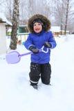 Szczęśliwy 3 roku berbecia z łopatą w zimie outdoors zdjęcie royalty free