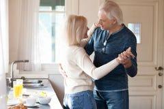 Szczęśliwy romantyczny starszy para taniec w kuchennym kulinarnym jedzeniu obraz royalty free
