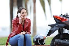 Szczęśliwy rowerzysta dzwoni ubezpieczenie obok jej motocyklu obraz royalty free