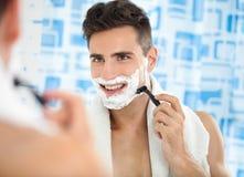 Szczęśliwy roześmiany mężczyzna goli jego twarz zdjęcia royalty free