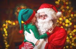 Szczęśliwy rozochocony dziecko elfa pomagier i Święty Mikołaj przy bożymi narodzeniami zdjęcia royalty free