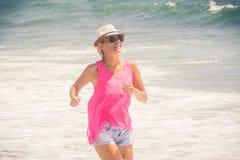 Szczęśliwy rozochocony kobieta bieg wzdłuż plaży przeciw oceanowi obrazy stock