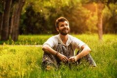 Szczęśliwy rozochocony mężczyzna obsiadanie na trawie przy parkiem Zdjęcia Stock