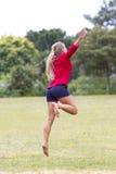Szczęśliwy 20s kobiety doskakiwanie dla szczęścia w pogodnym outdoors Obraz Stock