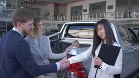 Szczęśliwy samochodowy sprzedawca radzi kupujących rodzinnych z dziecko dziewczyną w bagażniku pojazd i trząść ręki po pomyślnej  zdjęcie wideo