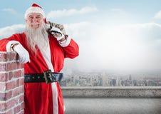 Szczęśliwy Santa Claus opiera na ścianie podczas gdy trzymający prezenta worek Obraz Royalty Free