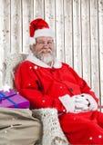 Szczęśliwy Santa obsiadanie na krześle z prezentami ilustracja wektor