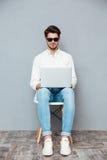 Szczęśliwy skoncentrowany młody człowiek siedzi laptop i używa w okularach przeciwsłonecznych obrazy stock