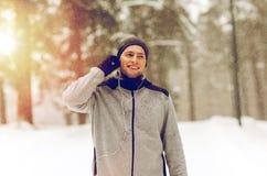 Szczęśliwy sporta mężczyzna z słuchawkami w zima lesie obraz royalty free