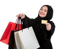 Szczęśliwy stać muzułmańskiej kobiety z torba na zakupy i kredytową kartą odizolowywającymi nad białym tłem Zdjęcie Royalty Free