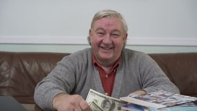Szczęśliwy starego człowieka obsiadanie przy drewnianym stołem z dolarami w jego rękach zamyka w górę Pozytywny bogaty człowiek d zdjęcie wideo