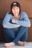 Szczęśliwy starej kobiety obsiadanie na podłogowym i uśmiechniętym zdjęcie royalty free