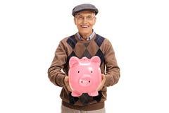 Szczęśliwy starsza osoba mężczyzna daje piggybank Fotografia Stock