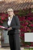 Szczęśliwy starszy agent nieruchomości patrzeje daleko od z domem w tle Zdjęcie Royalty Free