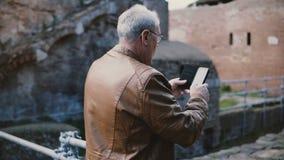 Szczęśliwy starszy Europejski mężczyzna bierze smartphone fotografię antycznego miasteczka ruiny w Ostia, Włochy na emerytura wak zbiory
