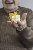 Szczęśliwy starszy kobiety mienia prezent na ona ręki Obrazy Stock