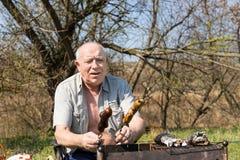 Szczęśliwy Starszy mężczyzna Skończony Piec na grillu Mięsnego Outside Obrazy Royalty Free