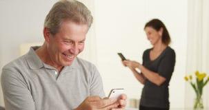 Szczęśliwy starszy mężczyzna używa smartphone obrazy royalty free